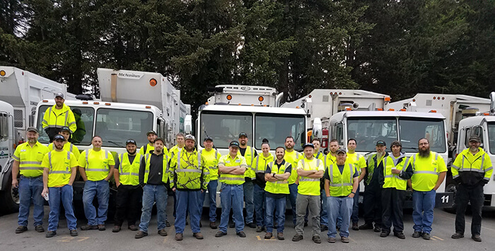 Mason County Garbage & Recycling drivers standing by hundreds of trash containers and holding a It Starts With One banner.